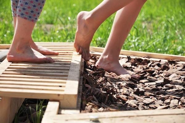 Летом для детей можно специально смастерить дорожки с разным покрытием для массажа стоп.